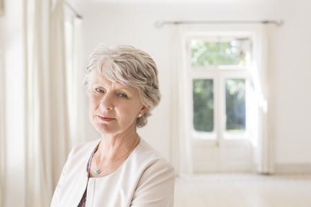 Older woman in empty living room LANG_EVOIMAGES