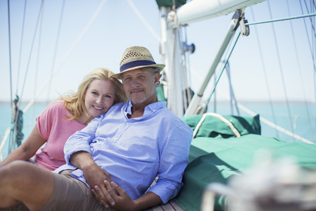 looking away from camera: Couple sitting on deck of sailboat