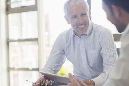 Businessmen laughing together in office LANG_EVOIMAGES