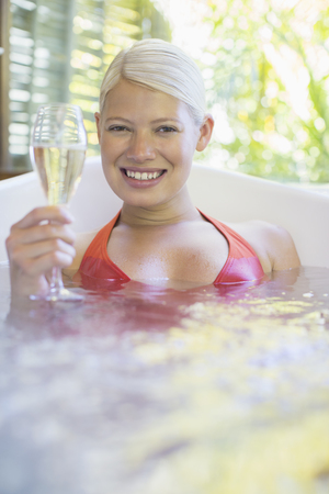 looking away from camera: Woman drinking white wine in hot tub