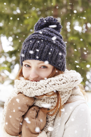 looking away from camera: Woman wearing scarf and hat in the snow