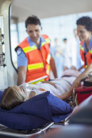 Paramedics examining patient on ambulance stretcher
