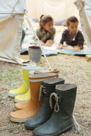 Rainboots lined up outside tent at campsite