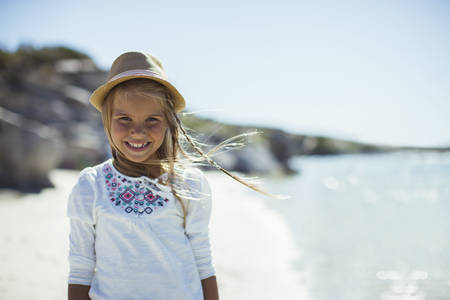 Young girl smiling on beach LANG_EVOIMAGES