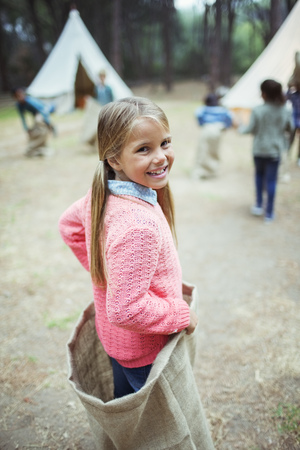 looking away from camera: Girl smiling in sack at campsite