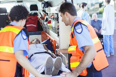 Paramedics examining patient in ambulance LANG_EVOIMAGES
