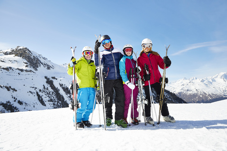 looking away from camera: Family carrying skis on mountain top