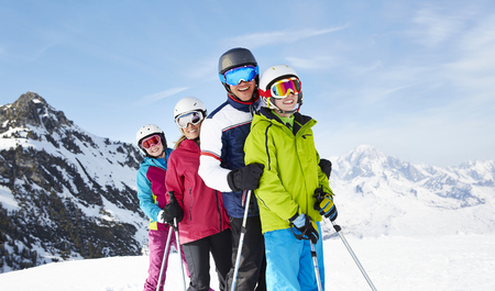 looking away from camera: Family skiing on mountain top LANG_EVOIMAGES