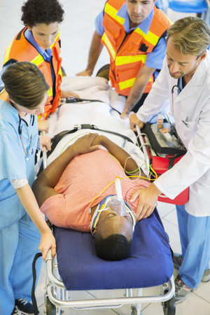 Doctor, nurse and paramedics examining man on stretcher