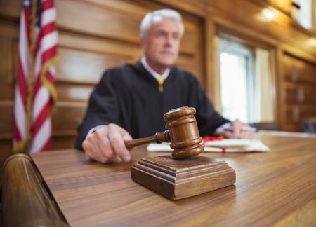pounding head: Judge holding gavel in court