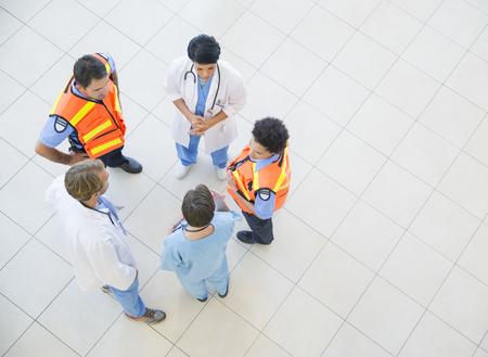 Doctors, nurses, and paramedics talking in hospital LANG_EVOIMAGES