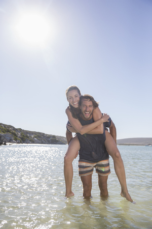 Woman being carried piggy back by boyfriend in waves