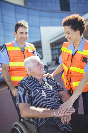 Paramedics talking to patient outside hospital LANG_EVOIMAGES
