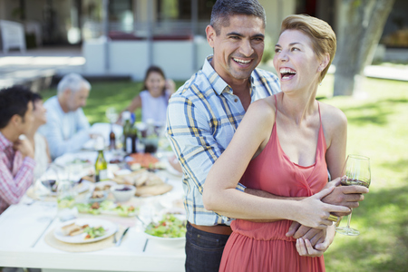 Laughing couple hugging outdoors