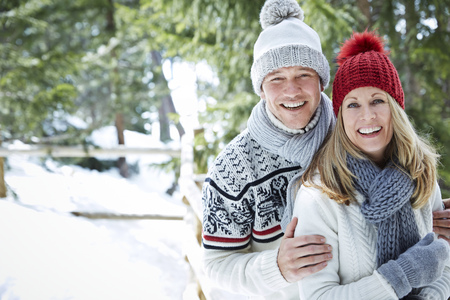 looking away from camera: Couple hugging in snow