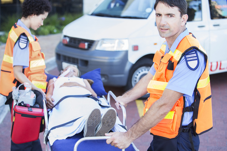 gurney: Paramedics wheeling patient on stretcher in hospital parking lot