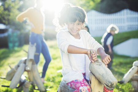 quarter horse: Girl smiling on rocking horse in playground