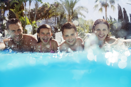 two piece swimsuit: Portrait of family with two children in swimming pool LANG_EVOIMAGES