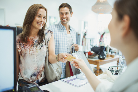 personal shopper: Couple paying with credit card in clothing store LANG_EVOIMAGES