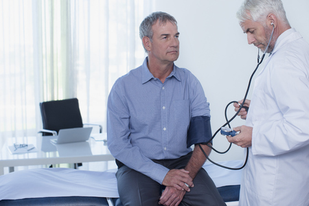 jalousie: Mature doctor taking patients blood pressure in office LANG_EVOIMAGES