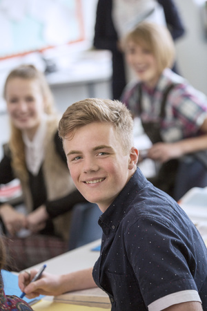 Portrait of smiling teenage student in classroom