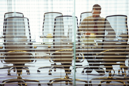 Businessman sitting behind blinds in conference room