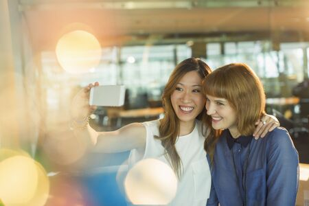 looking away from camera: Businesswomen taking cell phone selfie in office LANG_EVOIMAGES