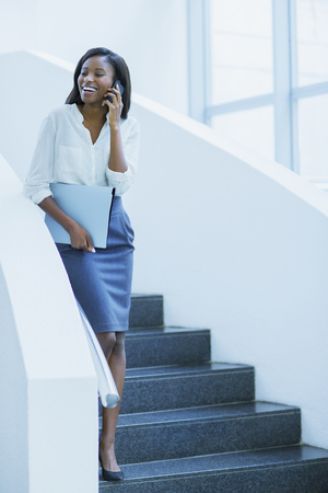 Businesswoman walking on cell phone on stairs of office building LANG_EVOIMAGES