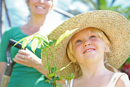 Girl wearing straw hat holding plant, woman with shovel in background LANG_EVOIMAGES