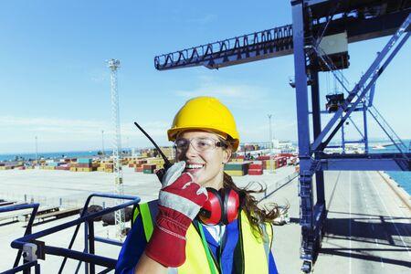 docker: Worker using walkie-talkie on cargo crane at waterfront