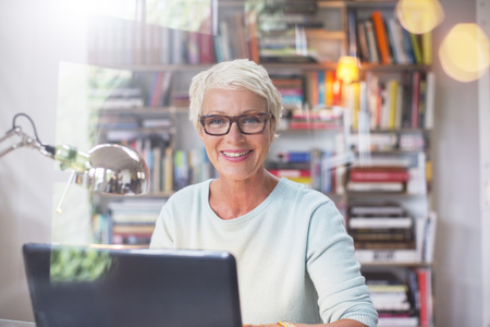 technology: Businesswoman smiling at computer in home office