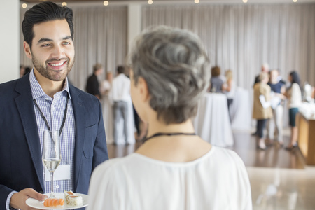 Businessman talking to businesswoman during reception in conference room, holding plate and champagne flute