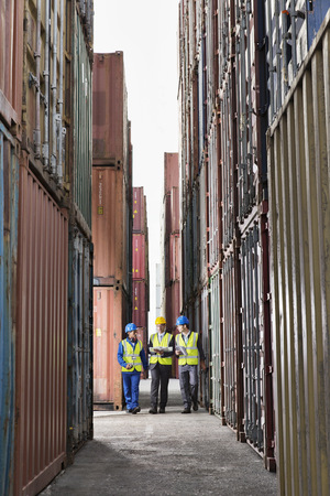 Workers talking between cargo containers LANG_EVOIMAGES