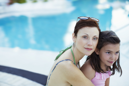 two piece swimsuit: Portrait of mother and daughter sitting by swimming pool LANG_EVOIMAGES
