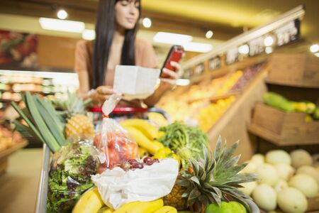 woman checking shopping list in grocery store stock photo picture