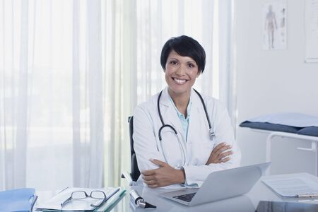 jalousie: Portrait of smiling female doctor sitting with arms crossed at desk with laptop
