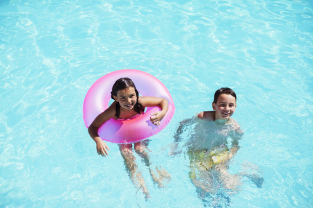 Portrait of brother and sister with pink inflatable ring in swimming pool LANG_EVOIMAGES