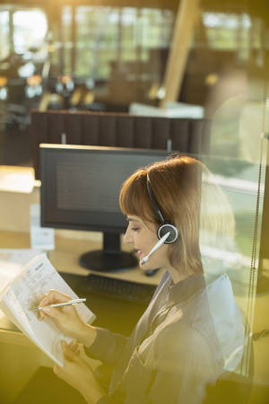 Businesswoman wearing headset and working in office