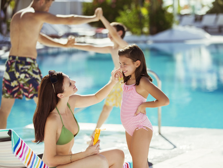 Mother applying suntan lotion on daughters face by swimming pool