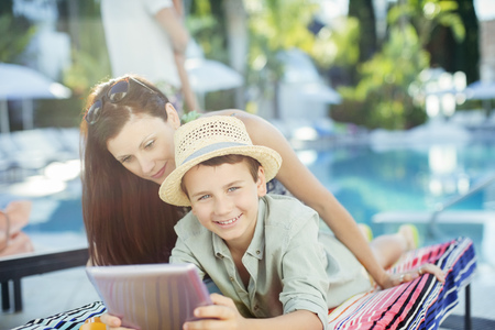 looking away from camera: Mother and son using tablet pc by swimming pool
