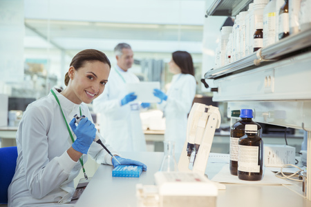 sample tray: Scientist pipetting samples into tray in laboratory LANG_EVOIMAGES