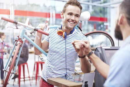 Man with bicycle fist bumping worker in cafe