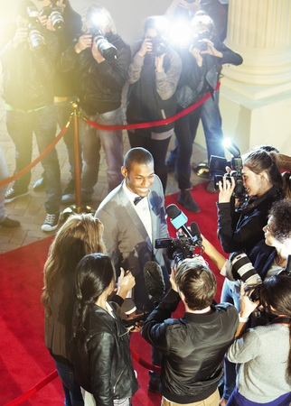 jamaican adult: Celebrity being interviewed and photographed by paparazzi photographer at red carpet event