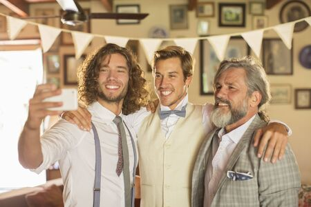 bridegrooms: Best man, bridegroom and father taking selfie in domestic room LANG_EVOIMAGES