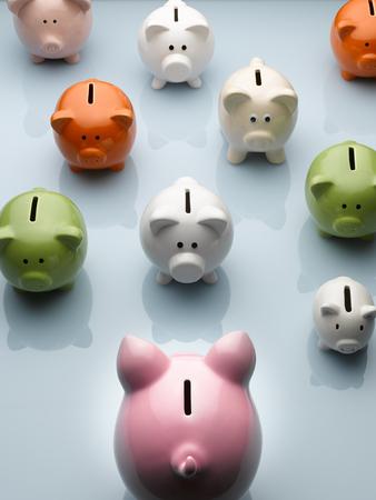 Large piggy bank facing smaller multicolor piggy banks still life LANG_EVOIMAGES