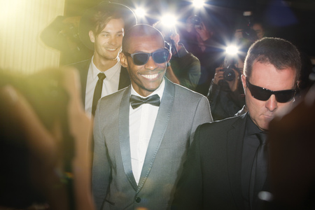 escorting: Smiling celebrity in sunglasses being photographed by paparazzi photographers at event