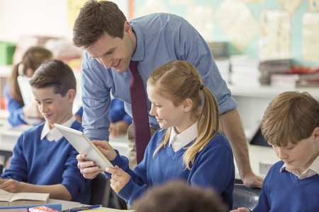 information medium: Teacher with his pupils in classroom using tablet pc