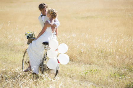 Bride and bridegroom riding bike with balloons attached LANG_EVOIMAGES