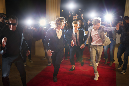 escorting: Enthusiastic celebrities arriving and running from paparazzi at red carpet event