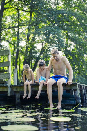 Father and sons dangling feet in lake